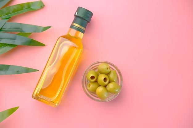 Flasche olivenöl und frische oliven in einem behälter auf rosa