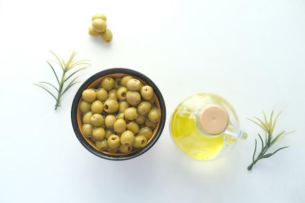 Flasche olivenöl und frische oliven in einem behälter auf weiß