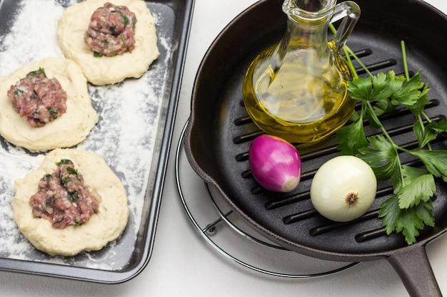 Flasche olivenöl, zwei zwiebeln und petersilie in der pfanne. füllung von fleisch auf rohen teigstücken auf backform. weißer hintergrund. ansicht von oben