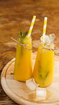 Flasche orangensaft mit eiswürfeln, selektiver fokus. hölzerner hintergrund. vertikales foto
