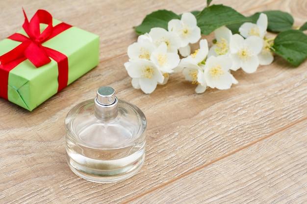 Flasche parfüm, geschenkbox mit rotem band und jasminblütenzweig auf den holzbrettern. konzept, an feiertagen ein geschenk zu machen. ansicht von oben.
