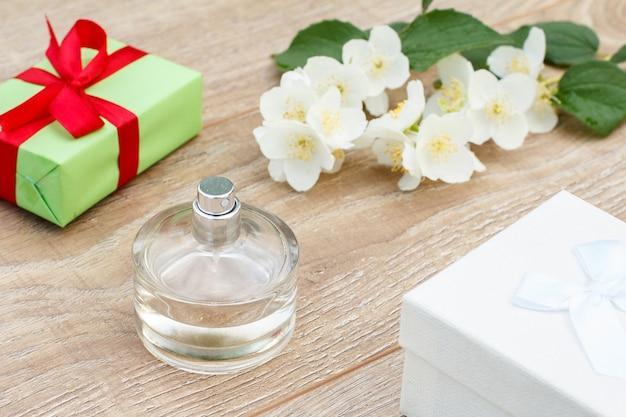 Flasche parfüm, geschenkboxen und jasminblütenzweig auf den holzbrettern. konzept, an feiertagen ein geschenk zu machen. ansicht von oben.