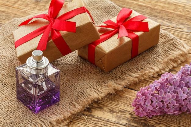 Flasche parfüm, geschenkboxen und lila blumen auf sackleinen und holzbrettern. konzept, an feiertagen ein geschenk zu machen. ansicht von oben.