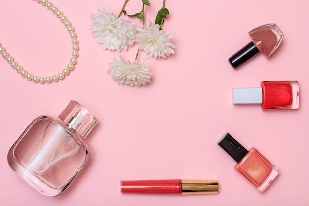 Flasche parfüm, perlen, lippenstift, flaschen mit nagellack und blumen auf rosafarbenem hintergrund. damenkosmetik und accessoires. ansicht von oben.
