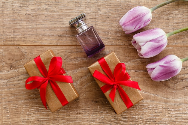 Flasche parfüm und geschenkboxen auf holzbrettern mit lila tulpen.