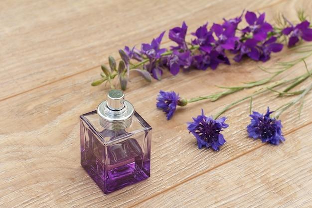 Flasche parfüm und lila blumen auf den holzbrettern. konzept, an feiertagen ein geschenk zu machen. ansicht von oben.