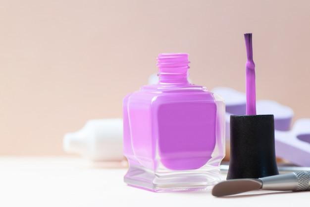 Flasche purpurrote nagellack- und manikürehilfsmittel auf einer tabelle.