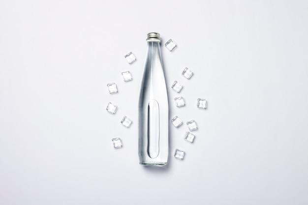 Flasche reines kristallwasser mit eiswürfeln auf einem weißen hintergrund unter sonnenlicht.