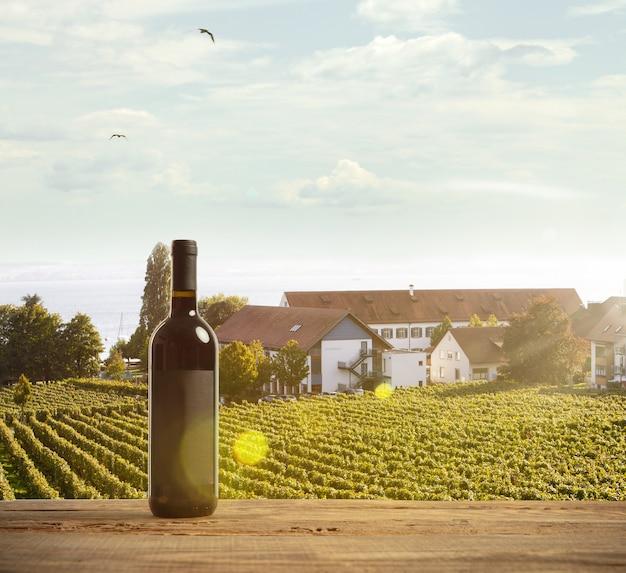 Flasche rotwein auf holzschiene mit ländlicher szene des landes im hintergrund. grüne blätter und ruhiger sommersonnenscheintag. exemplar. alkoholgetränke auf dem hinterhof des großen hauses