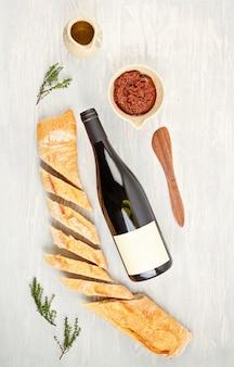 Flasche rotwein, brot und tomaten für buffetparty. traditionelles französisch oder italienisch führt zu einer flachen lage. draufsicht