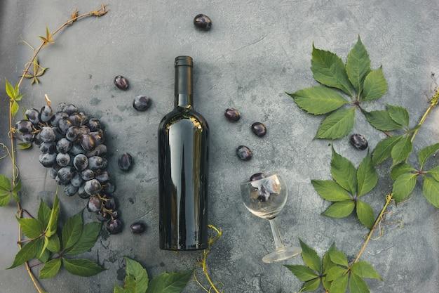 Flasche rotwein, grüne rebe, weinglas und reife traube auf dunklem steintischhintergrund der weinlese. draufsichtkopierraum für text. weinladen weinbar weingut oder weinprobe konzept.
