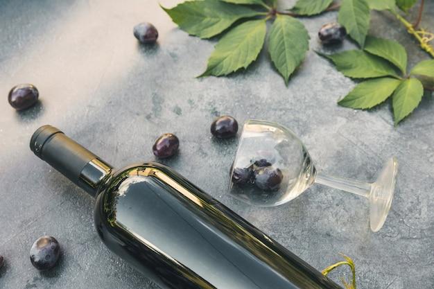 Flasche rotwein grünes weinglas und reife traube auf vintage dunklem steintisch hintergrund top...