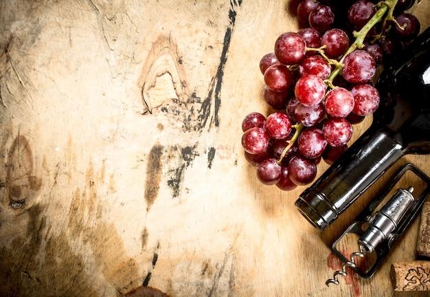 Flasche rotwein mit einem zweig trauben und einem korkenzieher auf hölzernem hintergrund