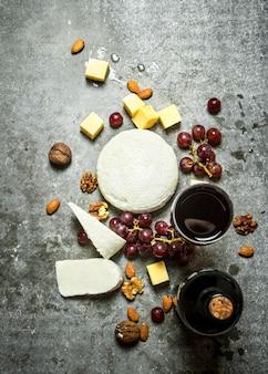 Flasche rotwein mit nüssen und käse. auf dem steintisch.