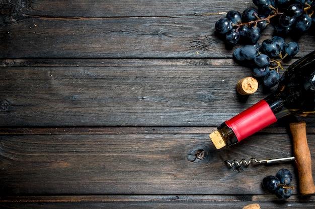 Flasche rotwein mit trauben. auf einem holz.