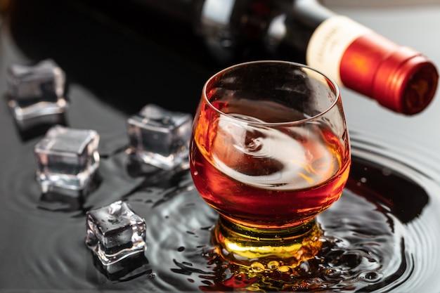 Flasche rotwein mit weinglas. wasserspritzen und -tröpfchen auf der schwarzen reflexion.