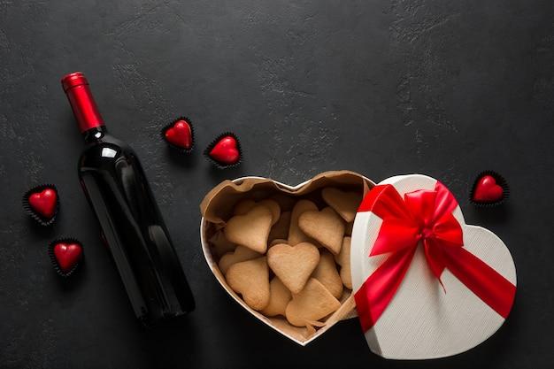 Flasche rotwein und herzplätzchen im geschenk auf schwarz. valentinstag grußkarte. von oben betrachten. platz für text.