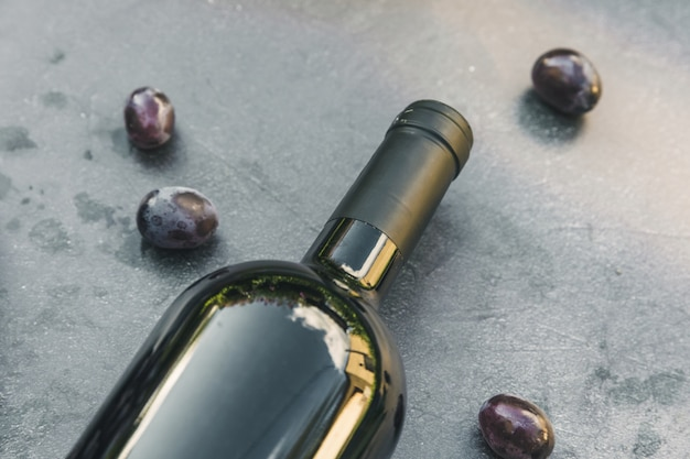 Flasche rotwein und reife traube auf dunklem steintischhintergrund der weinlese. draufsichtkopierraum für text. weinladen weinbar weingut oder weinprobe konzept.