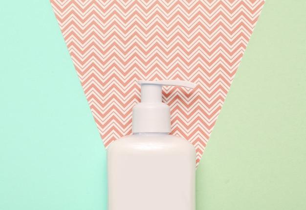 Flasche sahne auf pastellpapierhintergrund. draufsicht