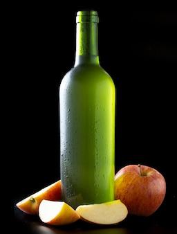 Flasche sehr kalter apfelwein mit äpfeln auf schwarzem