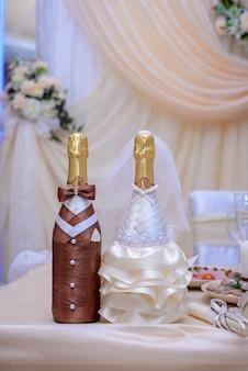 Flasche sekt in einer schönen hochzeitsdekoration in den kostümen von braut und bräutigam in beigetönen
