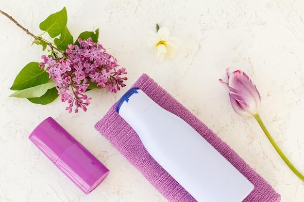 Flasche shampoo, handtuch, deodorant, tulpe und lila blüten auf strukturiertem hintergrund. damenkosmetik und accessoires. ansicht von oben.