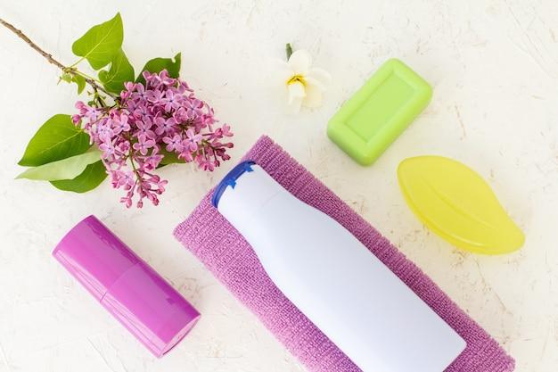 Flasche shampoo, handtuch, seife, deodorant und lila blüten auf strukturiertem hintergrund. damenkosmetik und accessoires. ansicht von oben.