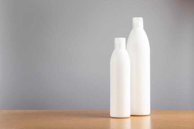 Flasche shampoo und haarspülung auf grauem hintergrund. reinigungsmittel für die haarpflege.