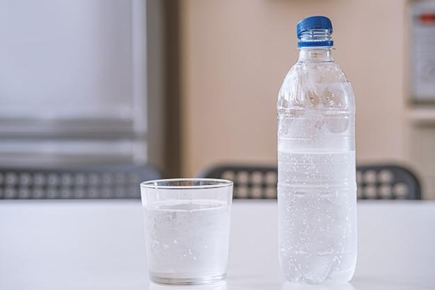 Flasche süßwasser hintergrundbeleuchtung auf hintergrund mit wassertröpfchen