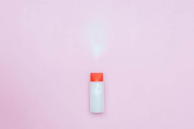 Flasche talkumpuder auf rosa hintergrund. pulver verschüttet aus weißem behälter