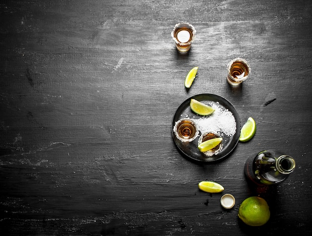Flasche tequila mit schnapsgläsern, frischer limette und salz. an der tafel.