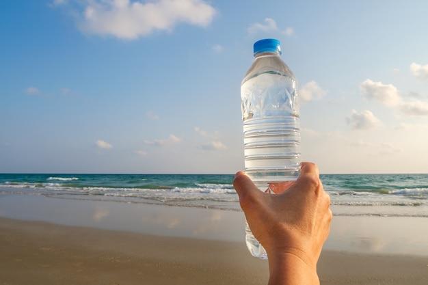 Flasche trinkwasser in der hand der frau.