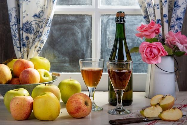 Flasche und gläser apfelwein mit äpfeln, nahe dem fenster, im rustikalen haus