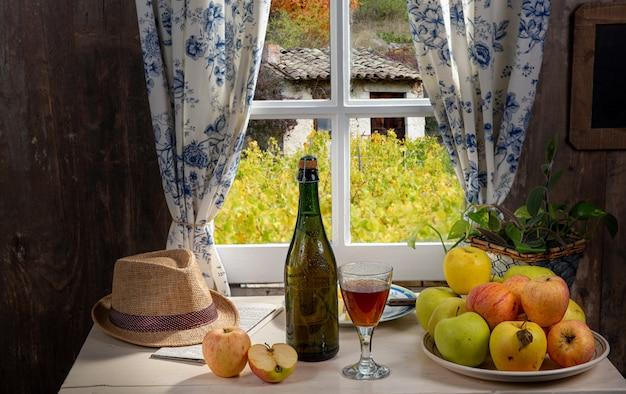 Flasche und glas apfelwein mit äpfeln. im rustikalen haus