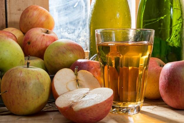 Flasche und glas apfelwein mit äpfeln