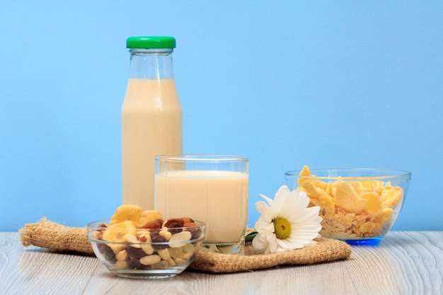Flasche und glas frische milch, glasschüsseln mit müsli und cornflakes auf sackleinen und blauem hintergrund.