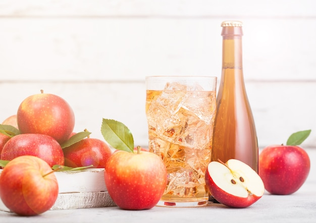 Flasche und glas hausgemachter bio-apfelwein mit frischen äpfeln auf weißem holzhintergrund