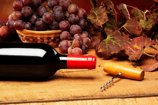 Flasche und glas mit rotweinkomposition auf einem rustikalen stillleben des holzbrettes