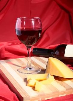 Flasche und glas mit rotweintrauben und käse auf holztisch.