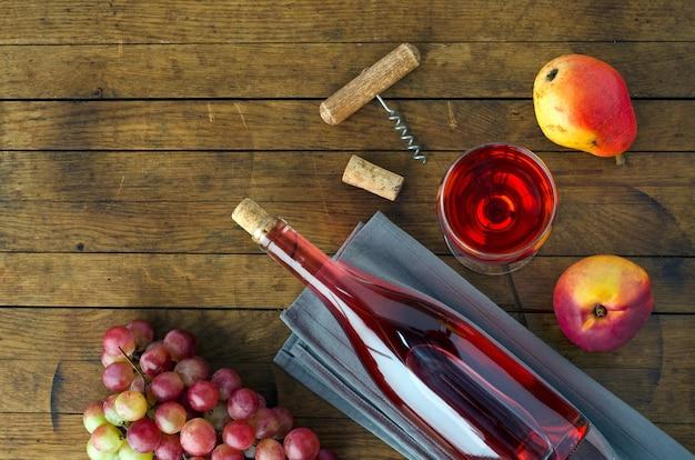 Flasche und glas mit wein, weintraube und früchten auf holztisch mit kopienraum für ihren text. ansicht von oben. flach liegen.
