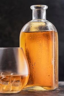 Flasche und glas mit whisky oder bourbon scotch auf dem tisch, tropfen auf dem dunklen glashintergrund. vertikales foto.