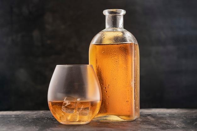 Flasche und glas mit whisky oder bourbon scotch auf dem tisch