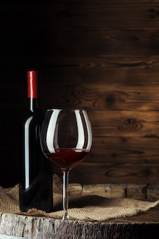 Flasche und glas rotwein auf hölzernem fass schossen mit dunklem hölzernem hintergrund