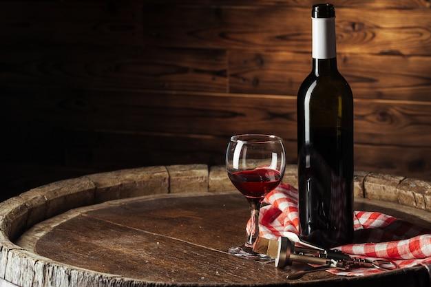 Flasche und glas rotwein auf hölzernem fass