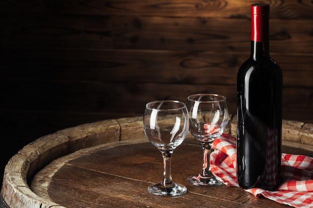 Flasche und glas rotwein auf hölzernem fassschuß