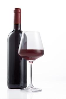 Flasche und glas spanischen rotweins auf weißer oberfläche