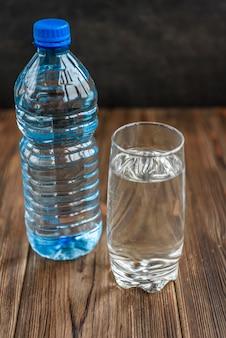 Flasche und glas wasser auf holzfläche.