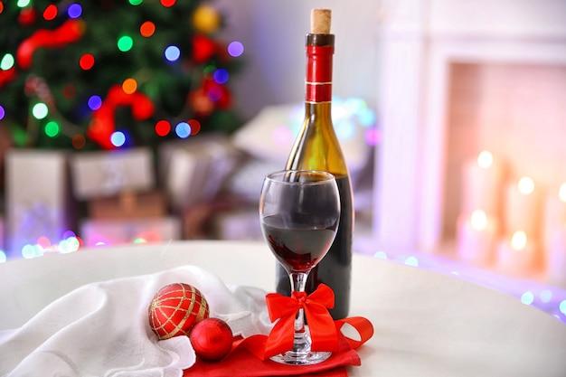 Flasche und glas wein mit weihnachtsdekor gegen bunte bokeh-lichteroberfläche