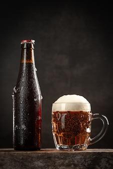 Flasche und krug bier auf holzsockel. vertikales format.