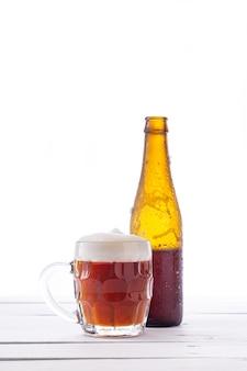 Flasche und krug bier auf weißem holzsockel. vertikales format.